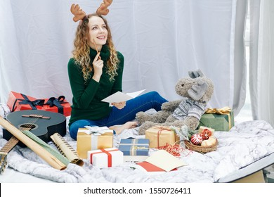 Smiling creative young woman writing Christmas poem in greeting card for friend
