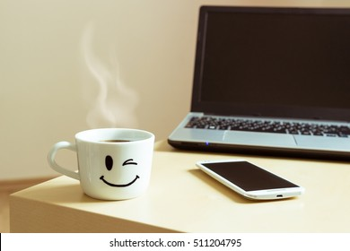 Smiling cup of coffee, smartphone and laptop on the desk