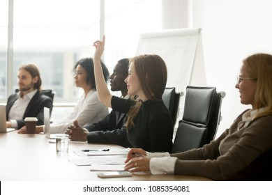 Smiling curious young businesswoman raising hand at multiracial group meeting engaging in offered activity, voting as volunteer or asking question at corporate business training, seminar or workshop