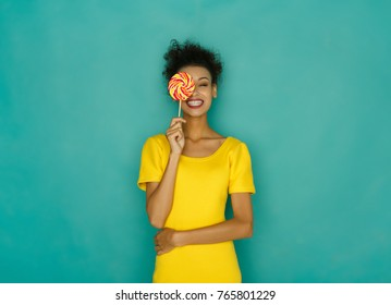 Smiling curly african girl in bright yellow dress holding candy lollipop. Young cheerful woman hiding out eye with lollipop at azur studio background, copy space. Sweet life and confectionary