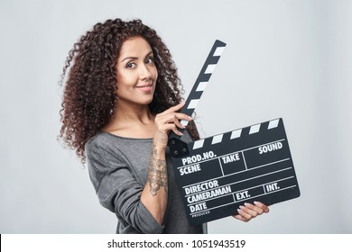 Smiling curly female holding movie clapper board, slate film.