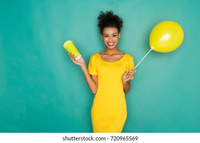 Smiling curly mulatto girl in bright yellow dress with take away coffee cup and balloon. Young cheerful woman at azur studio background, total yellow outfit, copy space