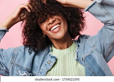 Lächelnde, lockige Frau in einer Denim-Jacke, die auf rosafarbenem Hintergrund steht. Freuvolles glückliches Mädchen in grünem tee Lachen auf isolierter Hintergrund