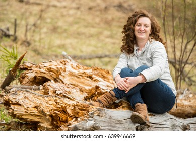 Smiling curly  woman sitting with crossed legs on a bark tree