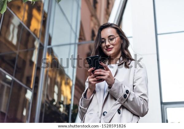 トレンディーなサングラスをかけた笑顔の巻き毛の女性が、街の中心街を歩き、電話を使う。白いジャケットを着たきれいな夏の女性が通りを歩き、携帯電話を見る