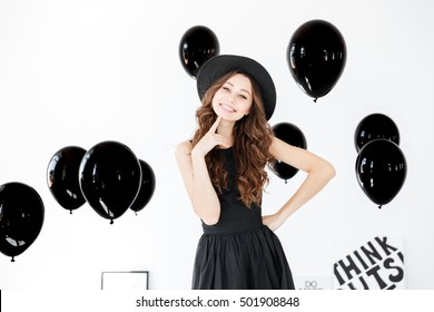 Smiling curly young woman in hat and dress wiith black balloons over white background