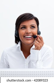 Smiling customer service agent with headset on against white background