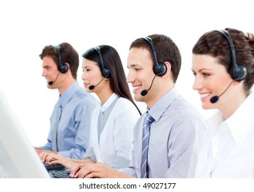 Smiling customer service agents working in a call center against a white background