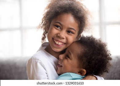 Smiling cute African American girl hug little toddler brother show love and affection, funny mixed race sister embrace sibling, holding in arms, black kids cuddle laughing, reconcile after fight