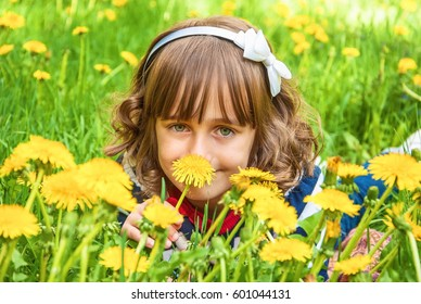 Smiling cute baby on spring lawn with dandelions