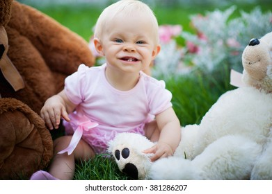 Smiling cute baby-girl on green grass with teddy bears toys