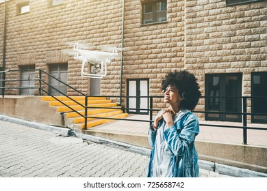 Smiling cute black girl is recording her video blog using modern flying drone: she is standing in the center of urban street and looking up into camera of quadrupter with facade of building behind