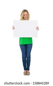 Smiling cute blonde holding white poster on white background