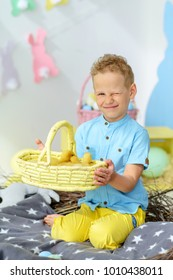 Smiling cute boy with a basket of ducklings. Easter concept.