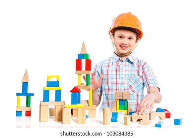 A smiling cute boy is building a toy block. Isolated on white background