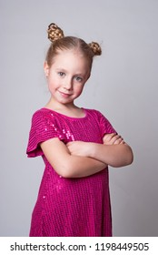 Smiling cute girl in а pink sparling dress  looking smart and serious