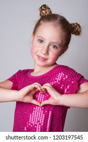 Smiling cute girl in а pink sparling dress shows heart hands sign