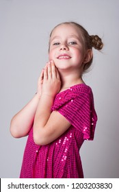 Smiling cute girl in а pink sparling dress   looking intellegent and adorable