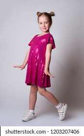 Smiling cute girl in а pink sparling dress modeling