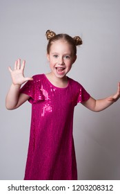 Smiling cute girl in а pink sparling dress dancing and singing a song waving hands