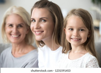 Smiling cute kid girl daughter looking at camera with young mother and old grandmother, happy little child posing for portrait with mom grandma, growing up in multi-generation 3 women family concept