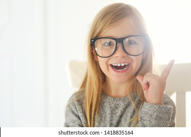 Smiling cute little girl with black eyeglasses over white background. Education, school, childhood, people and vision concept
