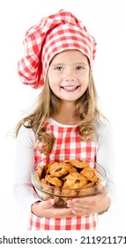 Smiling cute little girl in chef hat holding bowl with cookies isolated on a white