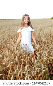 Smiling cute little girl child on field of wheat outdoor