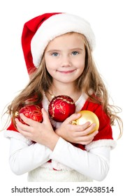 Smiling cute little girl with christmas balls and santa hat isolated on a white background