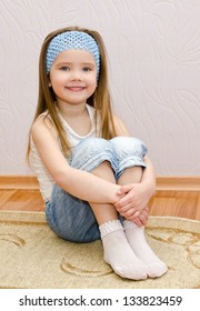 Smiling cute little girl sitting on a house floor