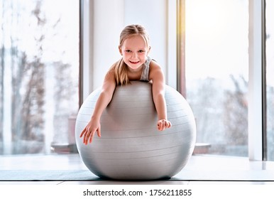 Smiling cute sportive girl looking at you while lying on the fitness ball in gym. Yoga, fitness, pilates for kids