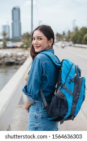 Smiling cute thai girl wearing jeans pant and jacket carrying blue bag on the road looking at camera.