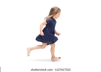 Smiling cute toddler girl three years running over white studio background. Caucasian model with long flowing hair in summer dress.