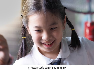 smiling cute Young asian girl with pig tail hair in primary school uniform playing  playdoh