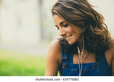 Smiling cute young girl listening to music. Horizontal outdoors shot.