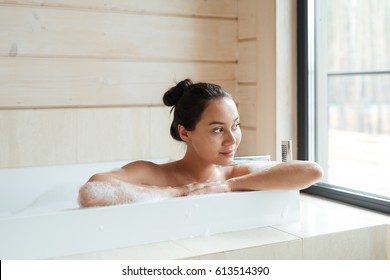 Smiling cute young woman sitting and looking at the window in bathtub with foam