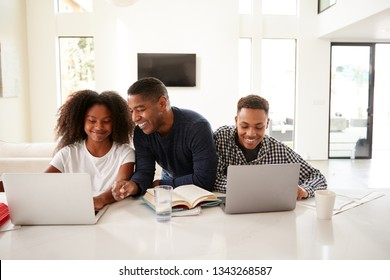Smiling dad helping his teen kids with their homework, front view, close up
