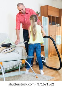 Smiling dad and his little daughter hoovering apartment together