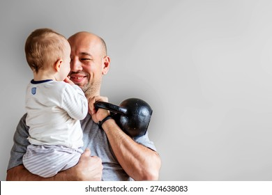 Smiling dad with his son and kettlebell in hands. Image with blur grey background