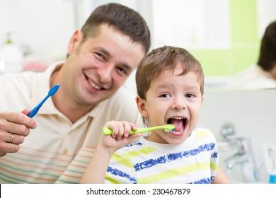 smiling dad and kid son brushing teeth in bathroom