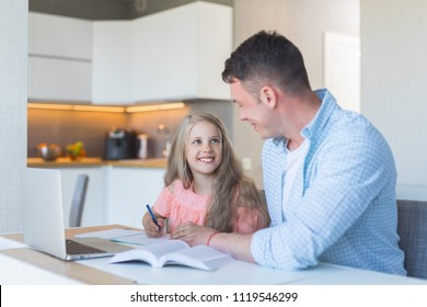 Smiling dad with a little daughter doing homework at home
