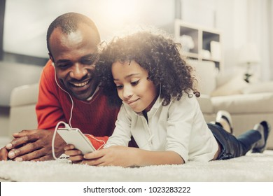 Smiling daddy and his daughter resting on carpet and looking at cellphone with headphones in ears