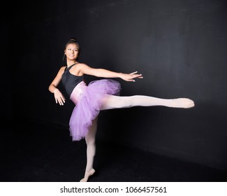 smiling dancer in purple tutu rehearsing