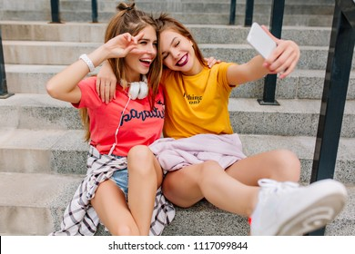 Smiling dark-haired girl making selfie while embracing with stunning sister in white headphones. Joyful blonde young woman in pink shirt posing with peace sign next to laughing friend relaxing outdoor