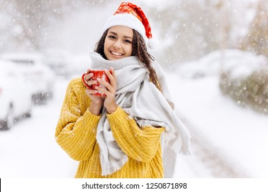 Smiling dark-haired girl in a yellow sweater, a white scarf  in Santa Claus hat is standing with a red mug on a snowy street on a winter day