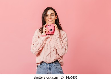 Smiling dark-haired lady in stylish sweater poses with pink camera on isolated background