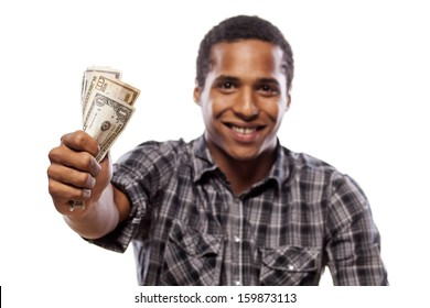 smiling dark-skinned young man shows a wad of cash in hand