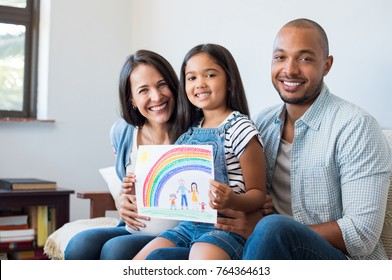 Smiling daughter showing painting of family with parents and beautiful rainbow. Happy child showing drawing of family with little brother. Cheerful pregnant woman with her family looking at camera.