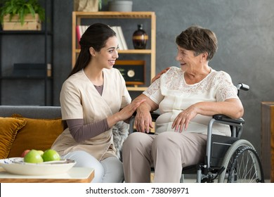 Smiling daughter sitting on sofa next to disabled elderly mother in wheelchair during meeting