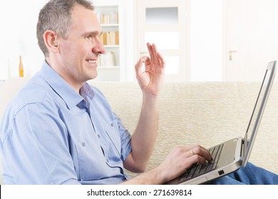 Smiling Deaf man talking using sign language on the laptop's cam